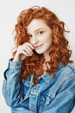 Portrait of cute young girl with red curly hair and freckles smiling looking at camera. Stock Image