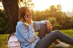 Portrait of a cute young girl sitting on a grass at the park. Talking on mobile phone Royalty Free Stock Image
