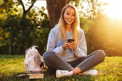 Portrait of a cute young girl sitting on a grass at the park. Using mobile phone Royalty Free Stock Image
