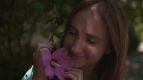 Portrait of a cute young girl sniffing and touching the purple hibiscus flowers. stock footage