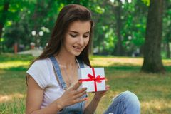 Portrait of a cute young girl who smiles and holds a small gift Royalty Free Stock Images