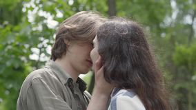 Portrait of cute young couple tenderly kissing close up. Happy girl and boy spending time together in the park. Leisure stock video