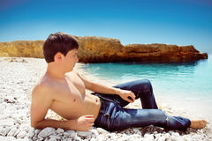Portrait of cute young man on the beach, blue sky Royalty Free Stock Photo