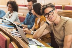 Dreamful male student sitting at lecture hall Stock Photo