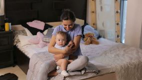 Portrait of a cute young mother hugging her little son in a cozy bedroom. Young mother with her 1 years old little son dressed in pajamas are relaxing in the stock video footage