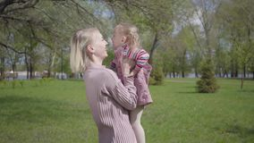 Portrait cute young mother spinning the daughter on hands on nature on spring day. Woman and kid playing in the park. Portrait young mother spinning the daughter stock video