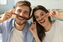 Portrait of cute young playful couple teasing with fake mustache sitting in sofa.  royalty free stock photography
