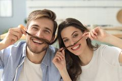 Portrait of cute young playful couple teasing with fake mustache sitting in sofa.  stock image