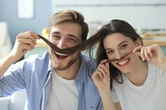 Portrait of cute young playful couple teasing with fake mustache sitting in sofa.  royalty free stock image