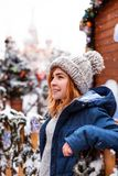 Cheerful young redhead woman on the street with Christmas background. Snowfall. Copy Space royalty free stock image