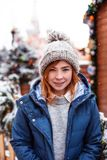 Cheerful young redhead woman on the street with Christmas background. Snowfall. Copy Space stock photos