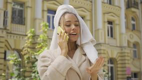 Portrait of cute young woman in bathrobe with towel on head talking by cellphone on the street. Confident girl enjoying. Portrait smiling young woman in bathrobe stock video