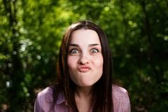 Portrait of cute young woman blowing lips kiss, grimacing for fu royalty free stock image