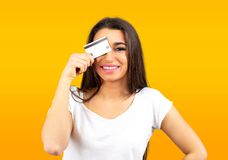 Portrait of a cute young woman casually dressed holding a credit card at her face. Isolated on yellow background stock photography