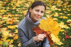 Portrait of cute young woman with a colorful bouquet of yellow autumn leaves in park in autumn. Fallen autumn leaves in the park and girl stock images