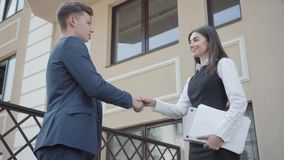 Portrait cute young woman and confident man in formal wear high five together on the terrace. Business relationship. Cute young woman and confident man in formal stock footage