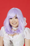 Portrait of cute young woman in doll costume and purple wig over red background Stock Photos