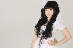 Portrait of cute young woman in doll costume standing over gray background Royalty Free Stock Photography