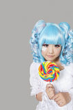 Portrait of cute young woman dressed as a doll holding lollipop over gray background Stock Photo