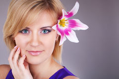Portrait of cute young woman with floewer near her face. Studio portrait Royalty Free Stock Images