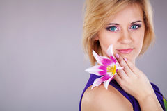 Portrait of cute young woman with floewer near her face. Studio portrait Royalty Free Stock Photography