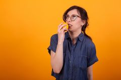 Portrait of cute young woman freaked out with orange in her hand over yellow background in studio. Girl with delicious orange stock photo