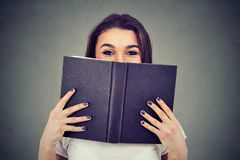 Portrait of a cute young woman hiding behind an open book and looking at camera stock photography