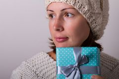 Portrait of cute young woman holding wrapped gift stock images