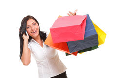 Portrait cute young woman mobile phone while holding shopping ba Royalty Free Stock Images
