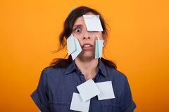 Portrait of cute young woman overwhelmed of work with sticky notes on her over yellow background in studio. Colorful sticky notes royalty free stock photos