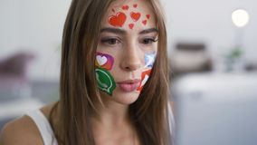 Portrait of cute young woman with painted social media icons on her face talking with her friend using camera on her. Tablet. Addiction to gadgets. Social media stock video