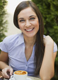 Portrait of cute young woman sitting and smiling in the. Closeup portrait of cute young woman sitting and smiling in the cafe with a cup of coffee Stock Image