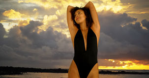 Portrait of cute young woman wearing swimsuit on sunset beach. Royalty Free Stock Images