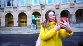 Portrait of cute Young woman who talks in videocall using mobile phone and shows beauty of city on winter day outdoors. Dazzling woman looks at screen of gadget stock video footage