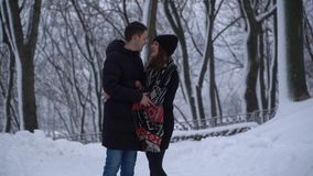 Portrait cute young woman in winter park under falling snow. Happy couple in love enjoys time together. Date of young stock video