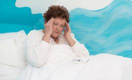 Portrait : défectuosité menteuse de femme supérieure avec le mal de tête dans le lit Image libre de droits