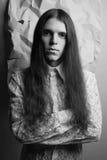 Portrait démodé d'un garçon aux cheveux longs au-dessus de papier froissé Photographie stock libre de droits