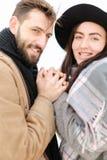 Portrait d'écharpe et de chapeau de port de sourire de couples à l'arrière-plan blanc Photos stock