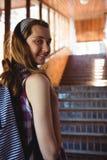 Portrait d'écolière dans le cartable tenant l'escalier proche Photos libres de droits