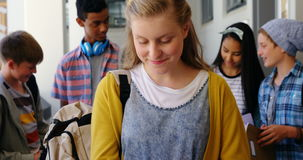 Portrait d'écolière de sourire se tenant avec le carnet dans le couloir clips vidéos