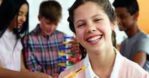 Portrait d'écolière de sourire tenant le crayon dans la salle de classe banque de vidéos