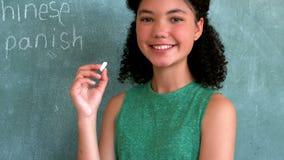 Portrait d'écolière feignant pour être un professeur dans la salle de classe banque de vidéos