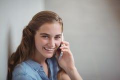 Portrait d'écolière heureuse parlant au téléphone portable dans le couloir Photo libre de droits