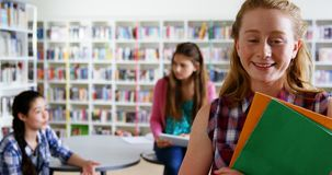 Portrait d'écolière heureuse tenant les livres 4k clips vidéos