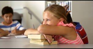Portrait d'écolière mignonne se penchant sur des livres dans la bibliothèque clips vidéos