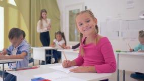 Portrait d'écolière sur la leçon de dessin dans la salle de classe légère se reposant derrière le bureau sur le fond des camarade banque de vidéos
