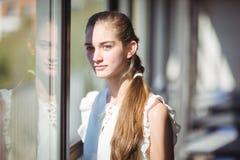 Portrait d'écolière tenant la fenêtre proche dans la salle de classe Photo stock