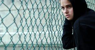 Portrait d'écolière triste dans la barrière proche debout à capuchon clips vidéos