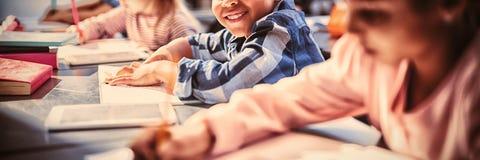 Portrait d'écolier de sourire faisant son travail dans la salle de classe image stock
