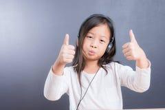 Portrait d'écouteur asiatique d'utilisation de petite fille et de téléphone intelligent Photos libres de droits